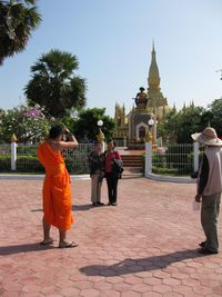 Laos - Vientiane - Tat Luoang - monk taking photo of friends during Tat Luonang Festival by PHKushlis 2009 10 31 168-1